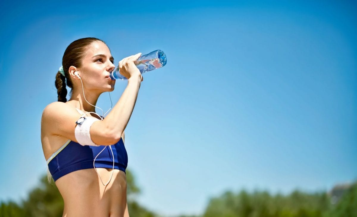 woman drinking a bottle of water in the sunshine