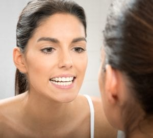 woman inspecting her teeth in the mirror