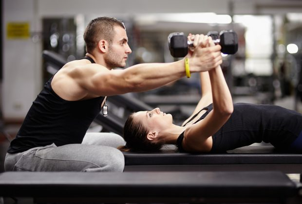 Man helps woman lifting weights