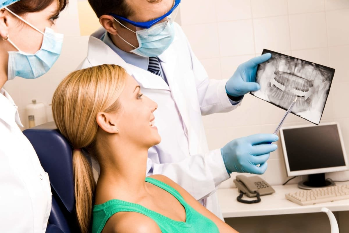 woman looking at panoramic x-ray with her dentist