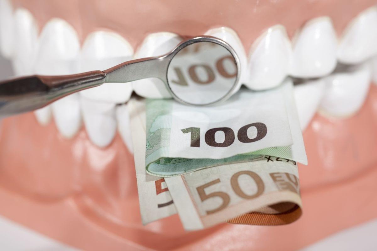 Money in front of teeth