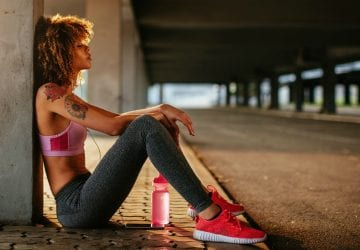 Woman resting in tunnel after run