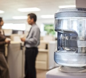 people standing in an office around a water cooler