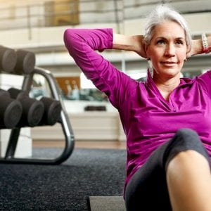 older woman doing core exercises at the gym