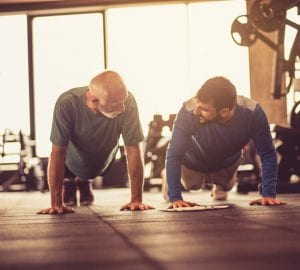 Personal trainer working exercise with senior man at gym.