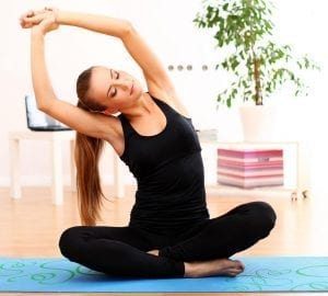 woman stretchin gon the floor sitting on a yoga mat