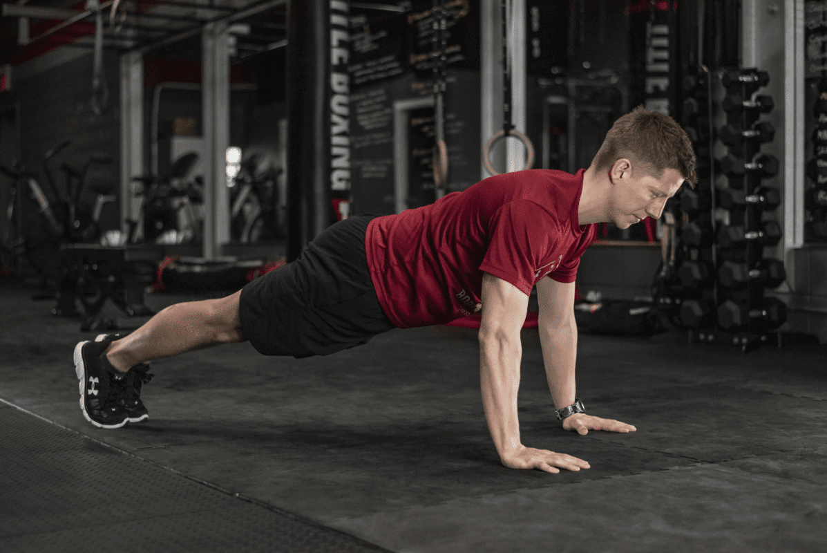man doing a plank exercise in the gym