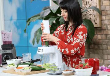 woman putting food through a food processor