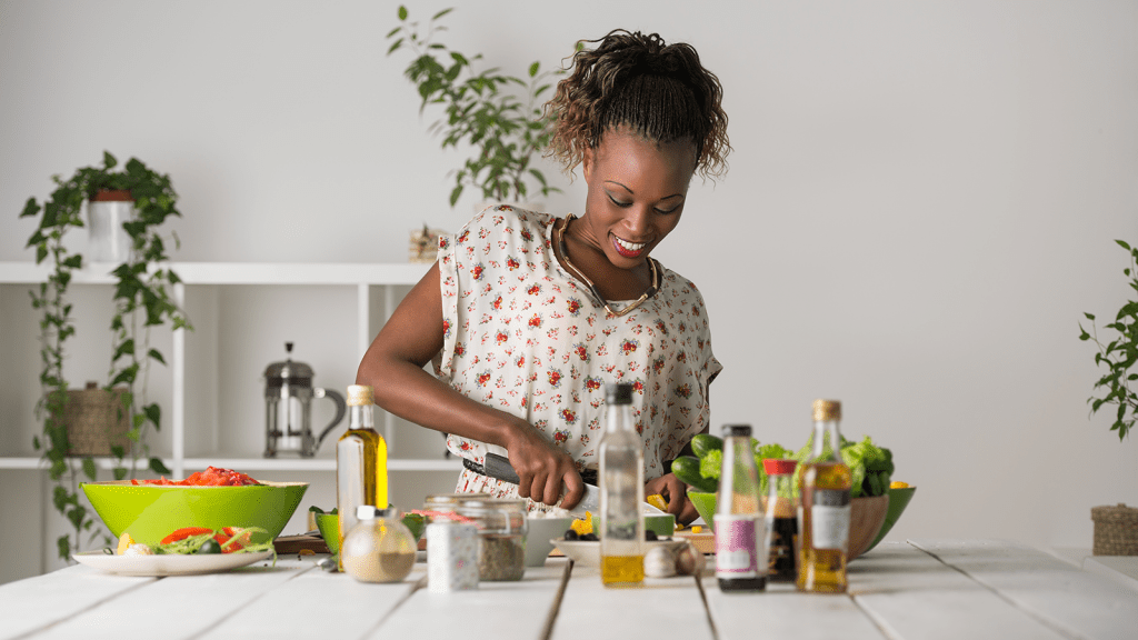 woman cutting vegetables at the kitchen counter
