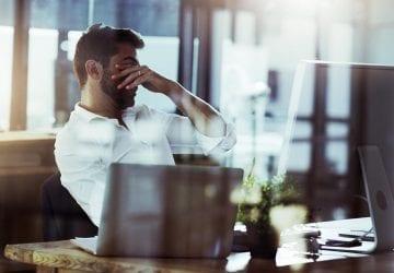 man sitting at his desk rubbing his eyes