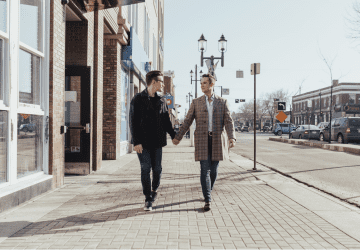 gay couple holding hands walking down a street