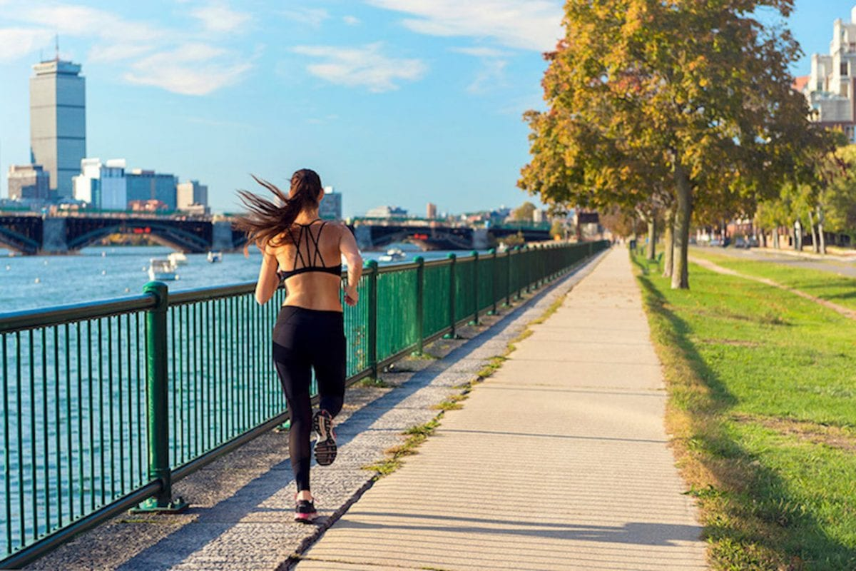woman running along a path next to water