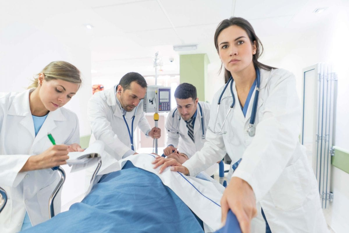 medical professionals in an ER room working on a patient