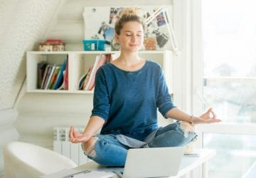 woman practicing yoga sitting on a table