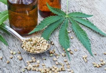 hemp leaves on wooden background, seeds, cannabis oil extracts in jars.