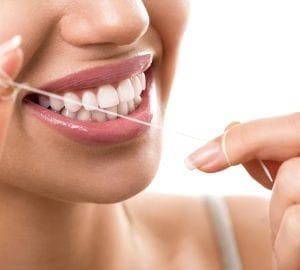 Cleaning teeth with dental floss, perfect healthy tooth