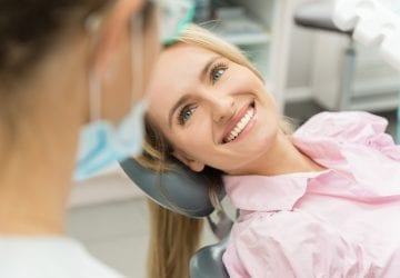 Horizontal color close-up headshot of woman having dental examination and sincerely smiling at dentist.