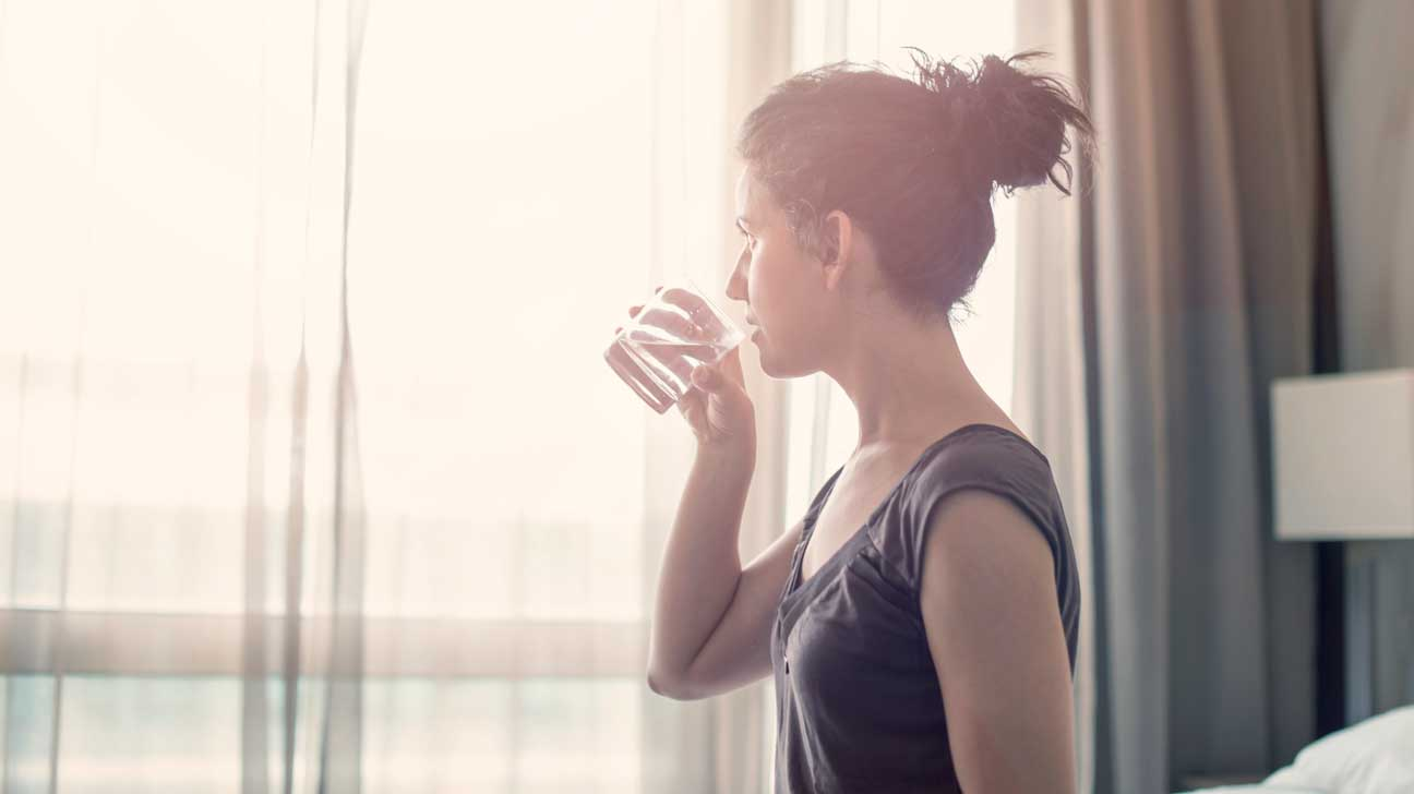 woman drinking a glass of water in the morning