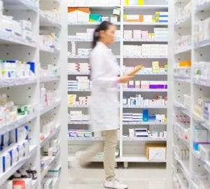 pharmacist walking in front of medicines