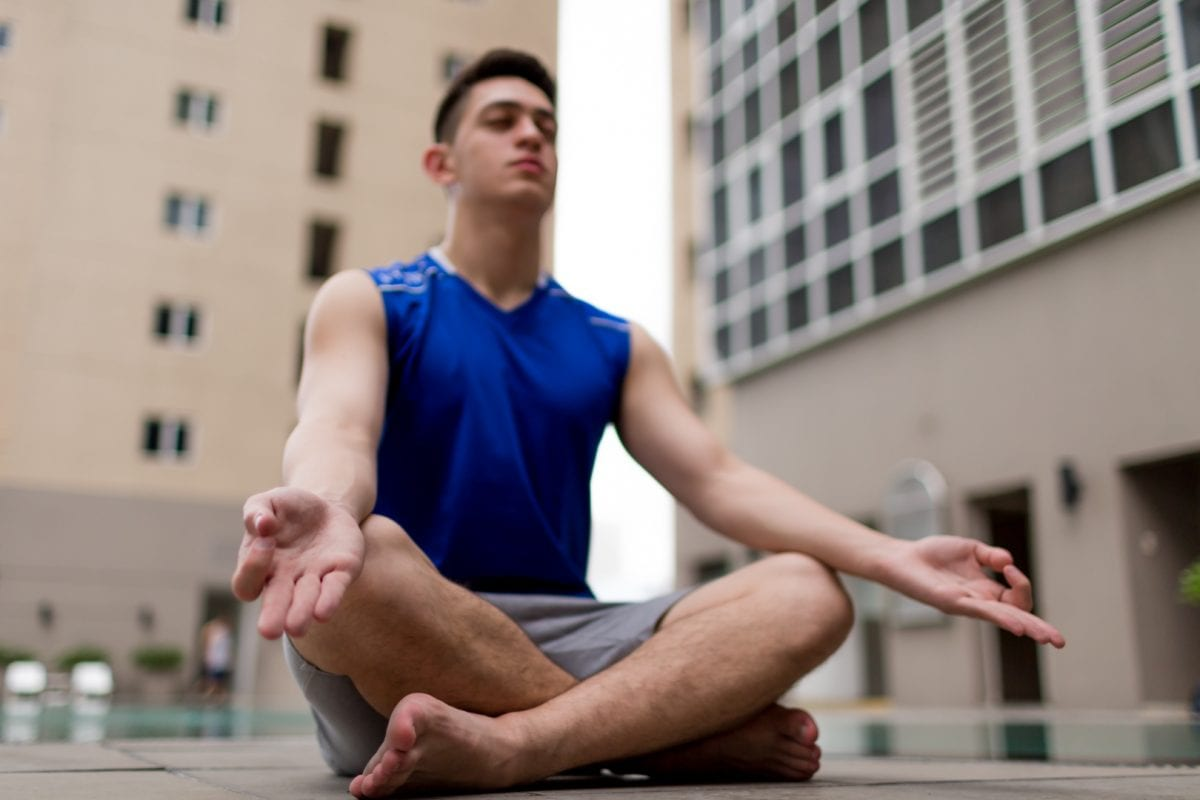 man meditating on a city street