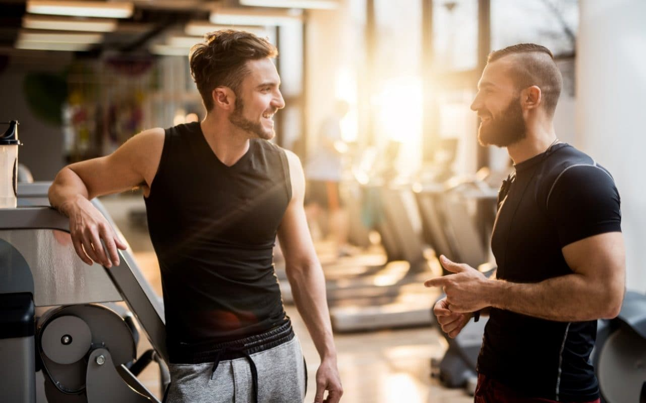 two men talking to each other at the gym