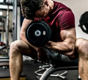 man doing arm curls with dumbell