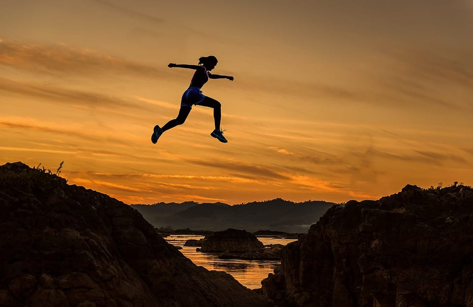 person jumping over a chasm at sunset