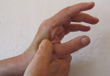 person applying pressure at acupressure point on hand