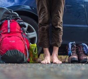 person with bare feet standing next to their hiking gear