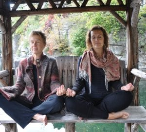 a pair of women meditating while sitting outdoors