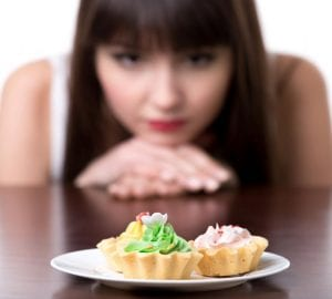 woman looking at a plate of sweets