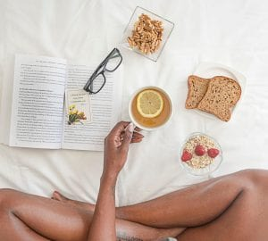 woman sitting on bed having breakfast and reading a book