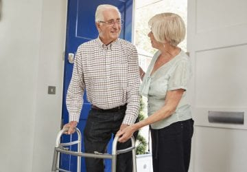 Senior couple at home talking, man using a walking frame