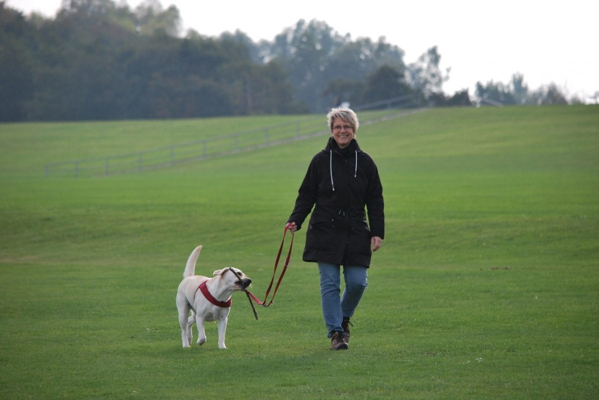 woman walking with her dog outdoors