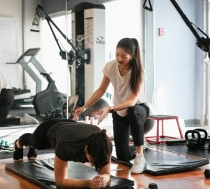 physical therapist working with their patient in the gym