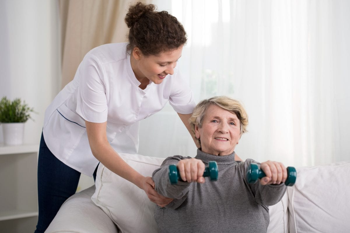 Old woman training with physiotherapist at home