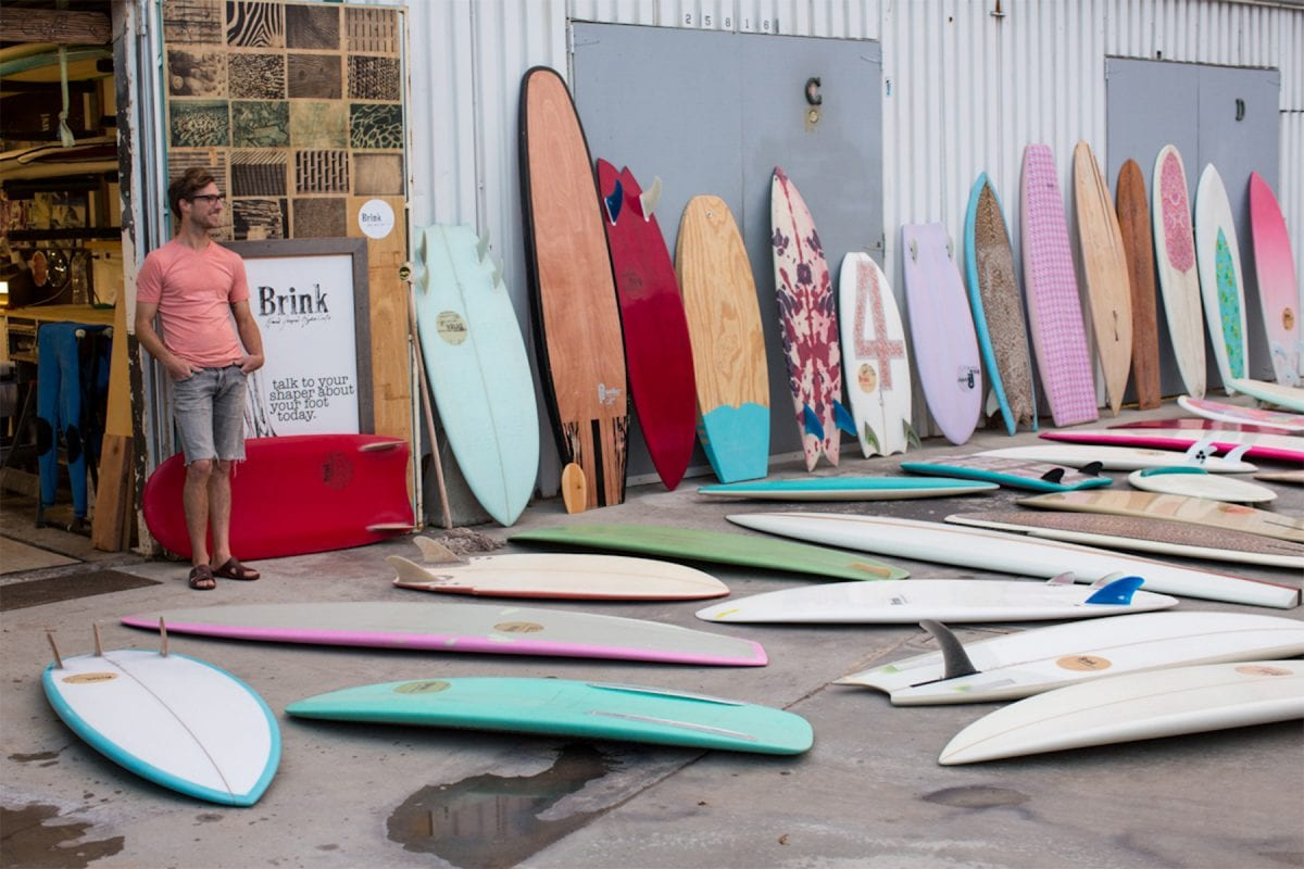 man standing beside a number of different surfboards
