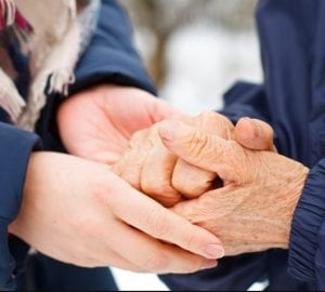 person holding the hands of an elderly person