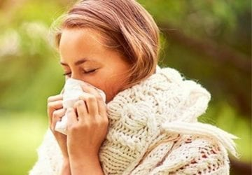 a woman outdoors sneezing into a kleenex