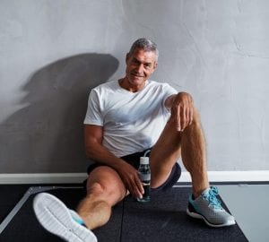 athletic man sitting on the floor smiling