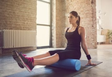 woman foam rolling on the floor of her gym
