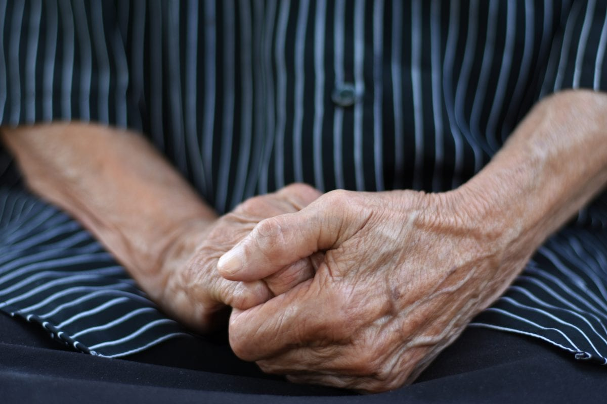 Close up of a midsection of an old woman, hand in hand in lap, wearing black short with white straps