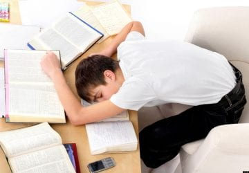 a boy asleep on his desk with books and paper scattered around him