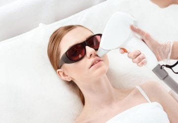 woman receiving laser hair removal on her face