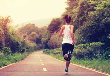 woman running on a forest pathway