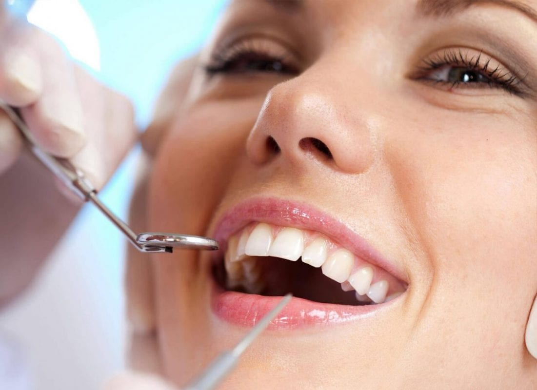 woman having her teeth fixed by a dentist
