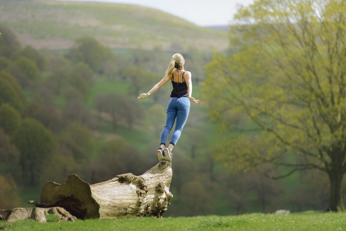 woman standing on the edge of a log lifting up to the sty