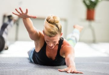 woman lying on the ground doing shoulder exercises