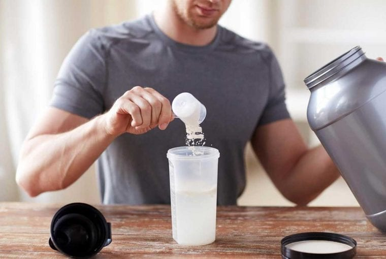 man taking a scoop of protein powder