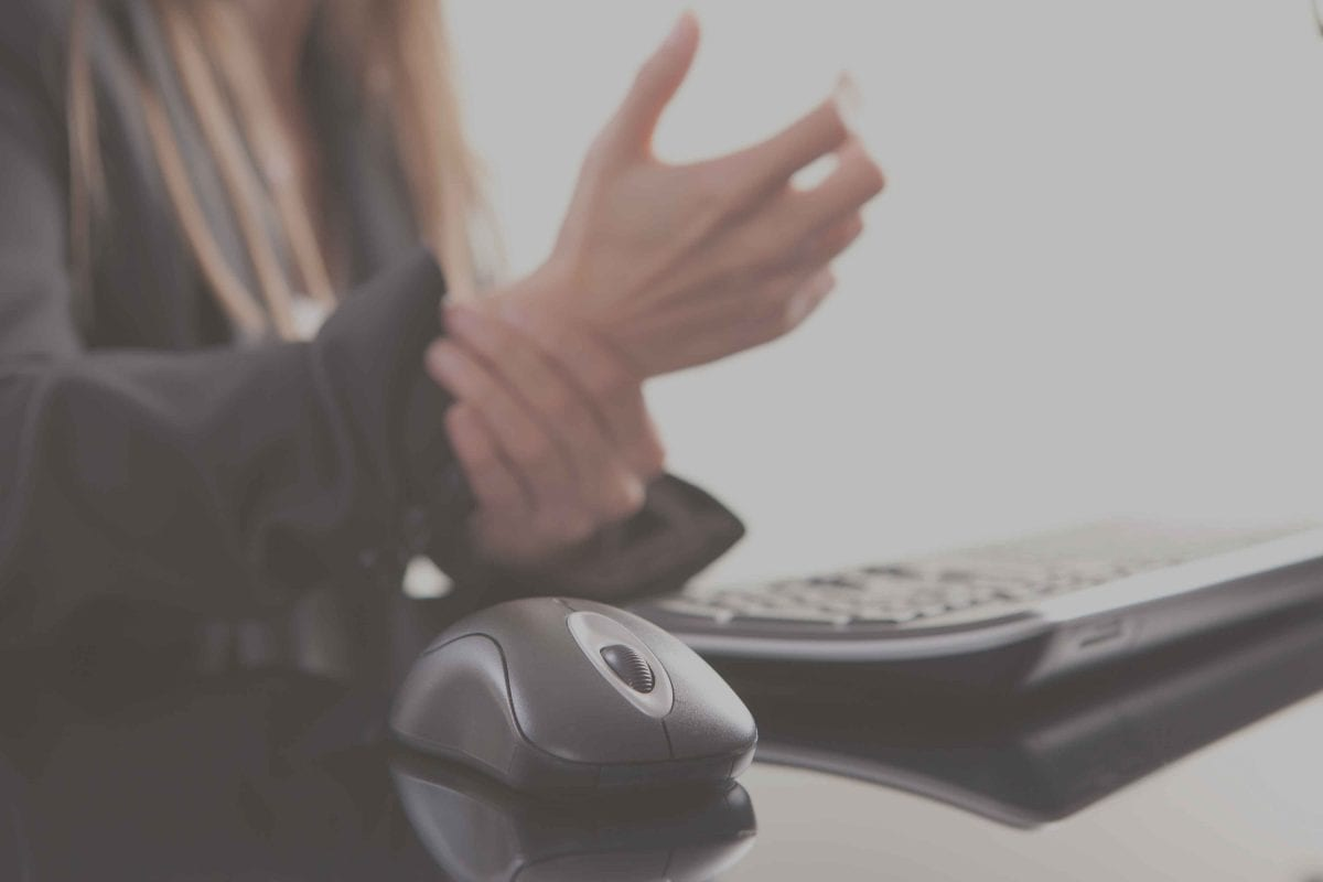woman rubbing her wrists next to her computer keyboard and mouse